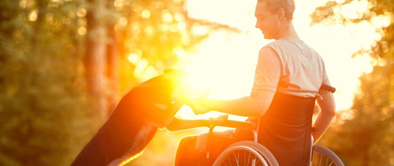 Mann im Rollstuhl mit Hund in der Reha